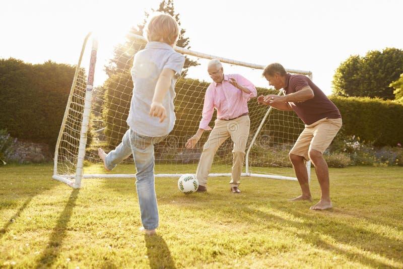 Três gerações masculinas de uma família que joga o futebol imagem de stock