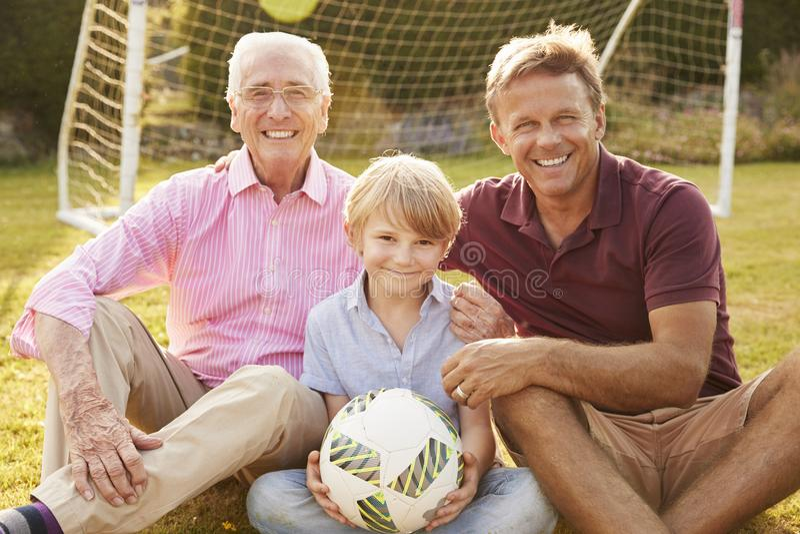 Três gerações masculinas de uma família sorriem à câmera fora fotos de stock royalty free