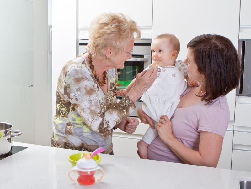 Três gerações na cozinha imagens de stock royalty free