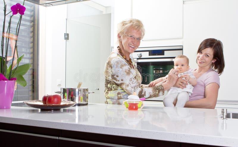 Três gerações na cozinha fotos de stock royalty free