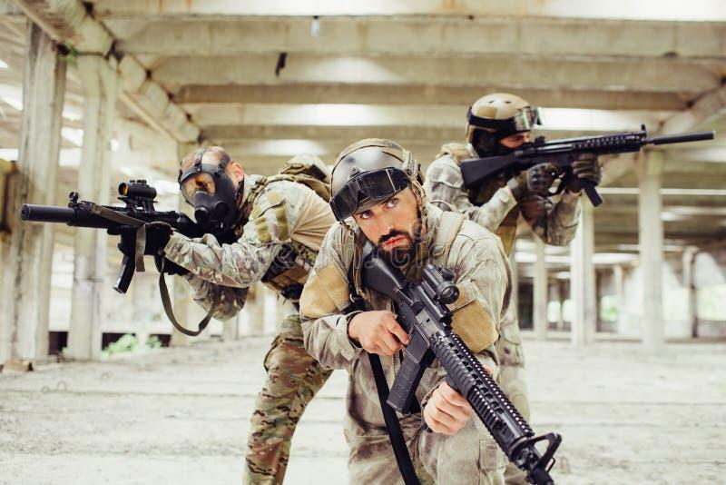 Três guerreiros estão levantando Dois deles olharem aos lados diferentes e tomarem o alvo através do rifle lenz quando o homem de imagens de stock royalty free