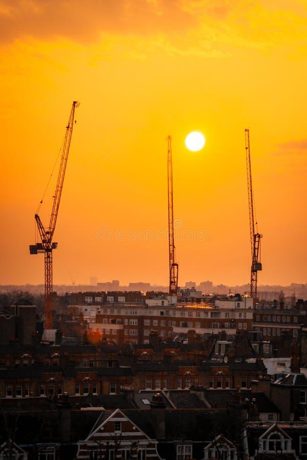Três guindastes vermelhos na cidade com sol e por do sol no fundo imagens de stock