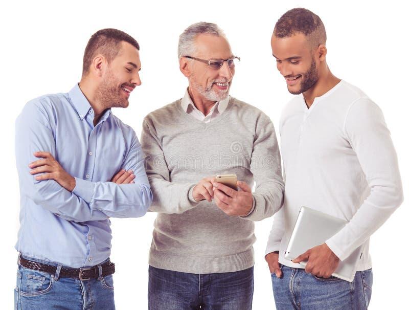 Três homens de negócios com dispositivos foto de stock royalty free