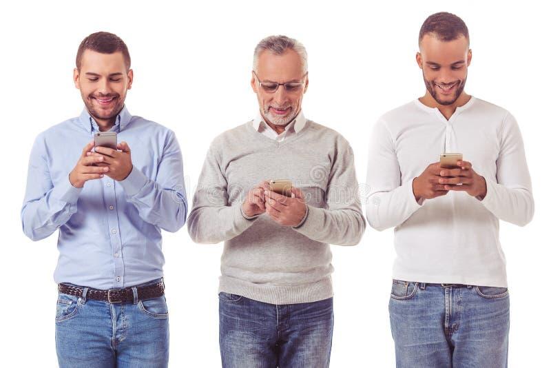 Três homens de negócios com dispositivos imagens de stock royalty free