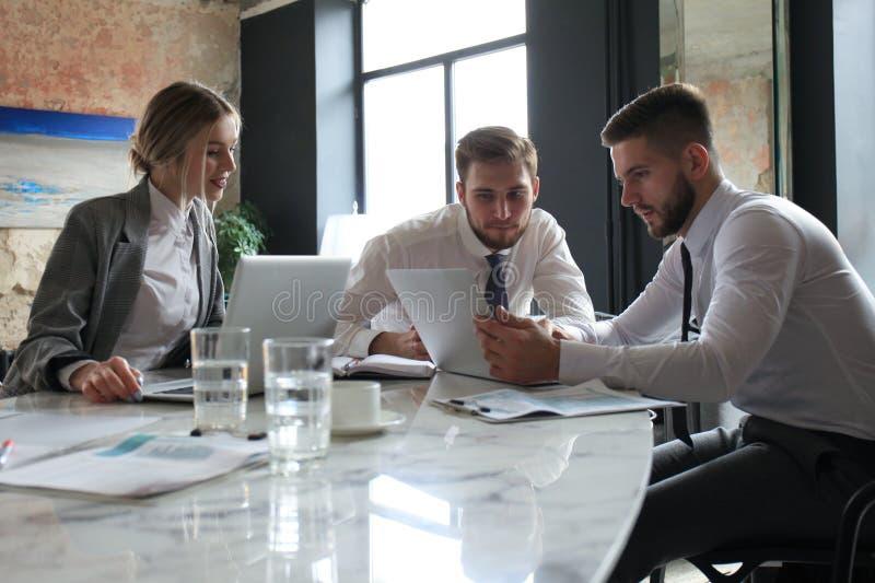 Três homens de negócios novos que discutem o negócio em uma reunião do escritório imagem de stock royalty free