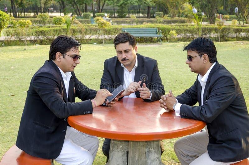 Três homens de negócios que discutem o plano de negócios no parque fotos de stock