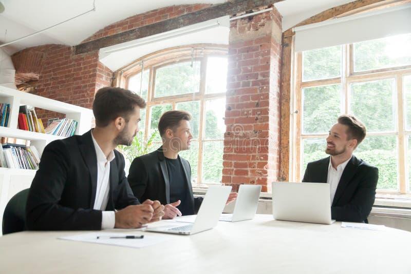 Três homens de negócios que negociam discutindo o negócio na conferência foto de stock