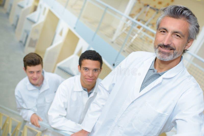 Três homens no uniforme branco imagens de stock royalty free