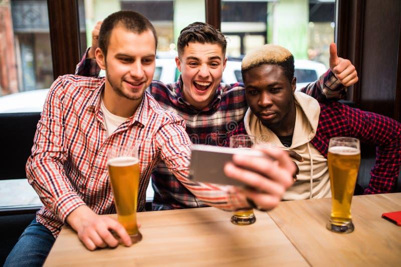 Três homens novos multirraciais na roupa ocasional estão tomando o selfie e a cerveja bebendo ao sentar-se no bar foto de stock royalty free
