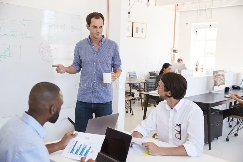 Três homens que discutem o negócio no whiteboard em um escritório ocupado foto de stock
