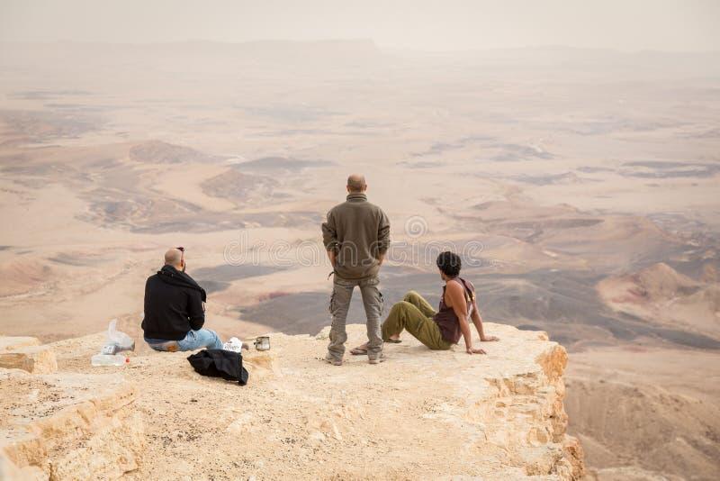 Três homens que olham o horizonte na borda do penhasco da cratera de Ramon no deserto do Negev, Israel imagem de stock royalty free