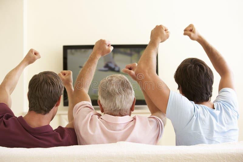 Três homens que olham a tevê do tela panorâmico em casa imagem de stock