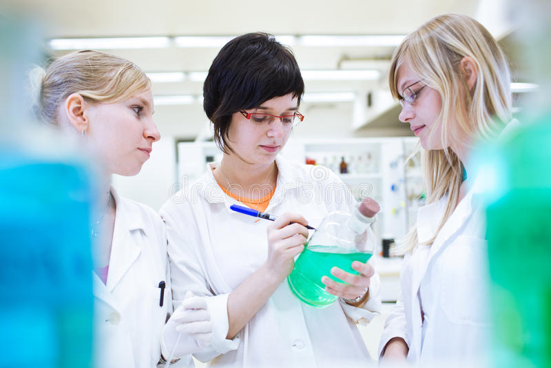 Três investigadores/estudantes da química em um laboratório imagem de stock royalty free