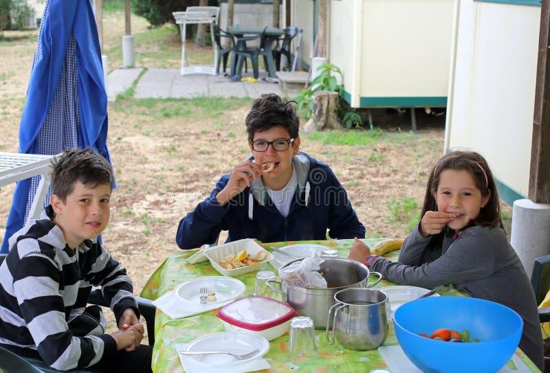 Três irmãos amigáveis ao jantar na tabela no bungalow imagens de stock royalty free
