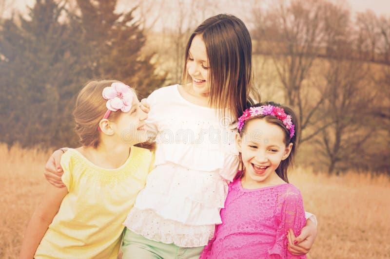 Três irmãos da menina que riem o sorriso imagem de stock royalty free
