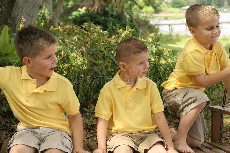 Três irmãos no balanço imagens de stock
