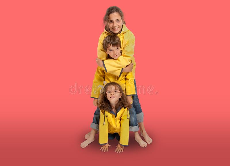 Três irmãos novos em capas de chuva amarelas fotos de stock royalty free