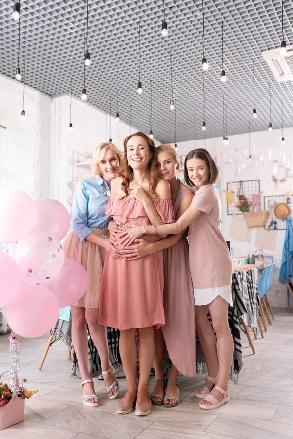 Três irmãs mais novas que abraçam sua irmã de antecipação imagens de stock