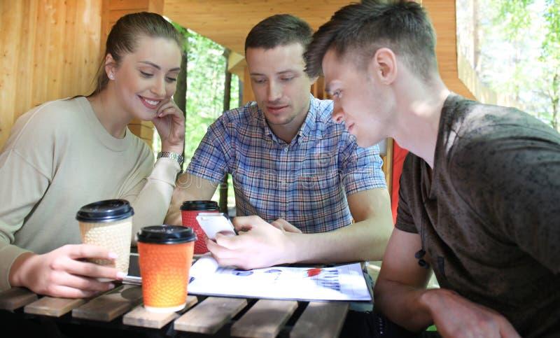Três jovens alegres que encontram e que usam o smartphone com o portátil no café exterior fotos de stock
