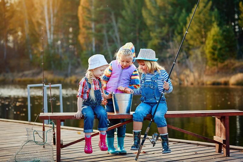Três jovens crianças vangloriam-se sobre os peixes travados na isca Conceito da amizade e o fim de semana ou as férias do diverti imagens de stock royalty free
