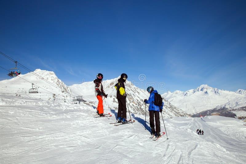 Três jovens esquiadores em máscaras espelhadas em cima em um dia ensolarado imagem de stock