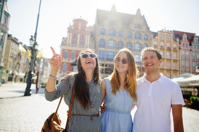Três jovens estão no quadrado da cidade antiga imagem de stock