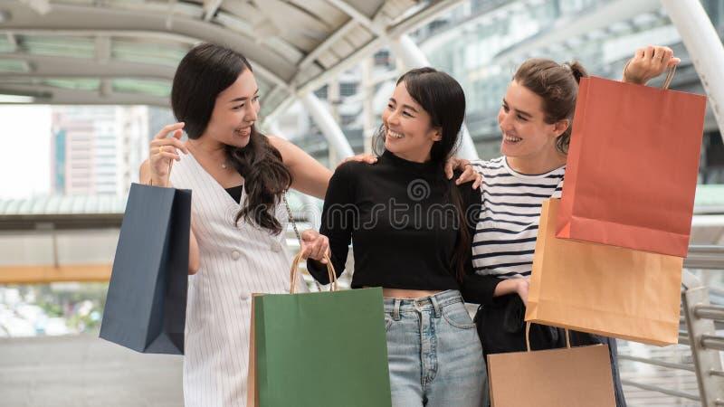 Três jovens mulheres bonitas que apreciam a compra na cidade imagens de stock royalty free
