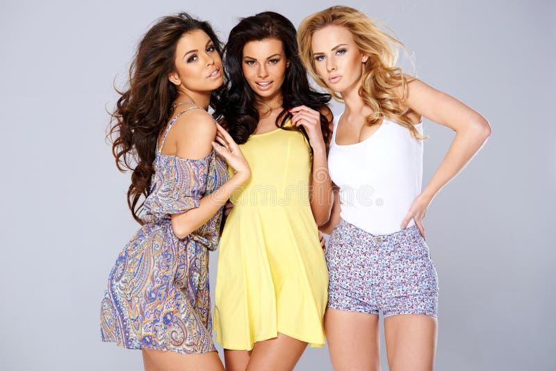 Três jovens mulheres chiques 'sexy' na forma do verão fotos de stock royalty free