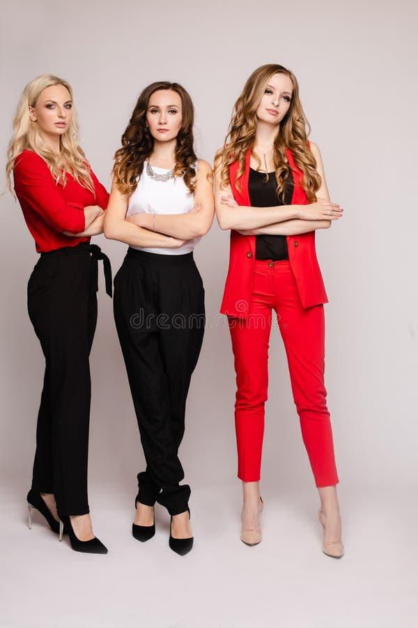 Tr?s jovens mulheres elegantes lindos em ocasional vestem-se fotografia de stock