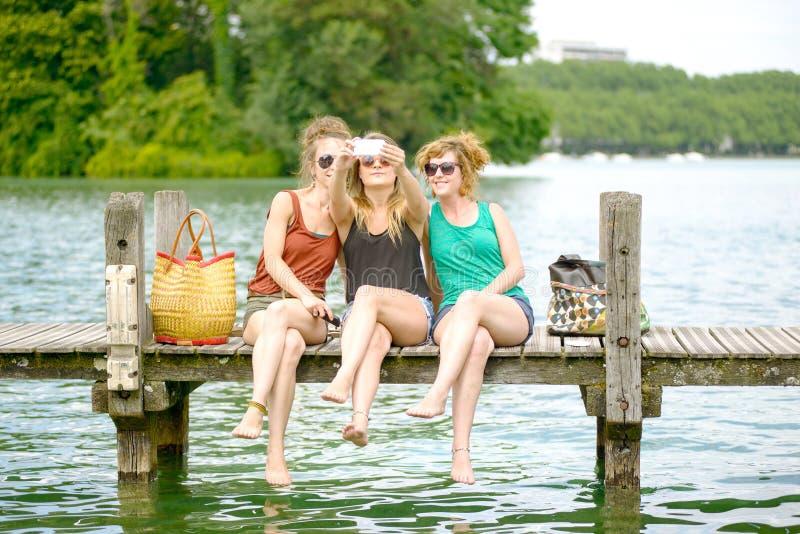Três jovens mulheres fazem o turismo em Annecy foto de stock