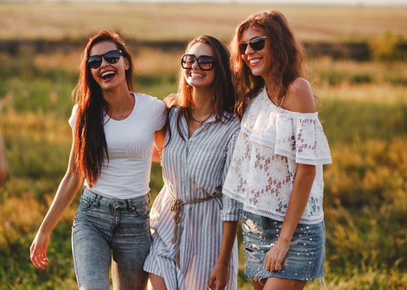 Três jovens mulheres lindos nos óculos de sol estão no campo e no sorriso em um dia ensolarado imagens de stock