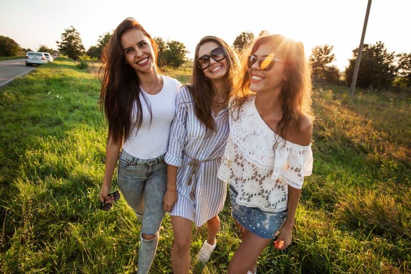 Três jovens mulheres lindos nos óculos de sol vestidos na roupa bonita estão no campo e no sorriso em um dia ensolarado imagem de stock royalty free