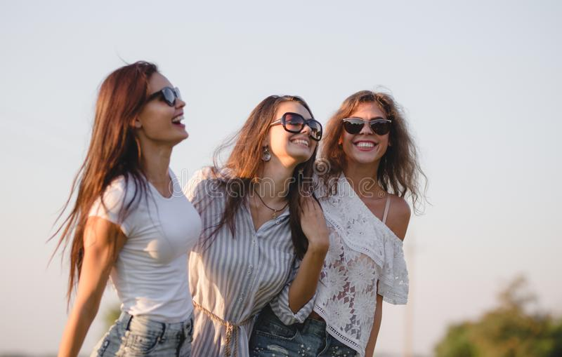 Três jovens mulheres lindos nos óculos de sol vestidos na roupa bonita são rir exterior em um dia ensolarado imagem de stock