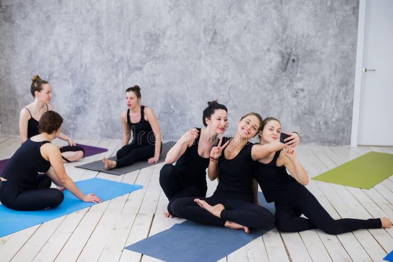 Três jovens mulheres que fazem o selfie após o exercício na classe da ioga fotografia de stock royalty free