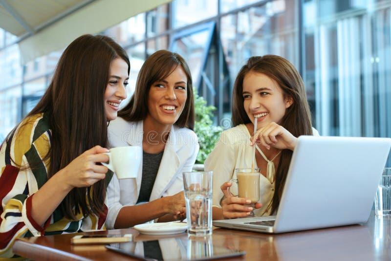 Três jovens mulheres que têm a conversação no café e que usam o portátil fotografia de stock royalty free