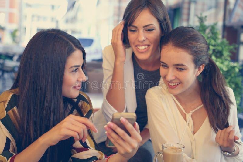 Três jovens mulheres têm a conversação do divertimento no café fotos de stock royalty free