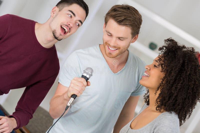 Três jovens que cantam no microfone imagens de stock