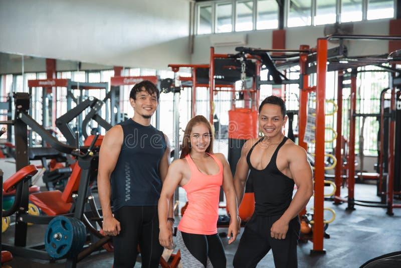 Três jovens que levantam no fitness center foto de stock