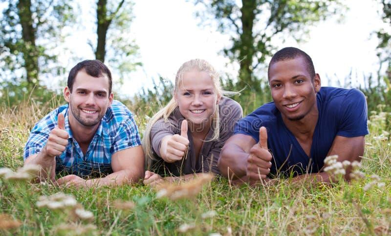 Três jovens que mostram os polegares acima fotografia de stock