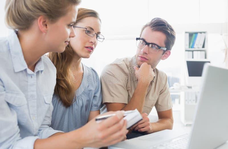 Três jovens que trabalham no computador fotografia de stock royalty free