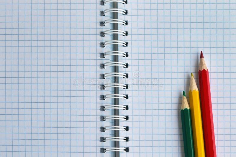 Três lápis coloridos em um caderno verificado close-up, vista superior fotografia de stock royalty free