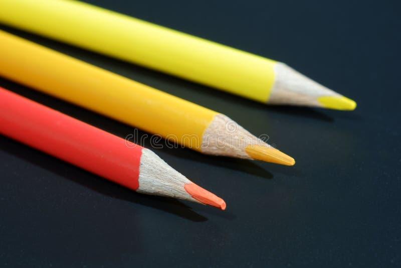 Três lápis coloridos no fundo preto foto de stock royalty free