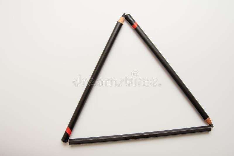 Três lápis pretos que formam um triângulo foto de stock royalty free