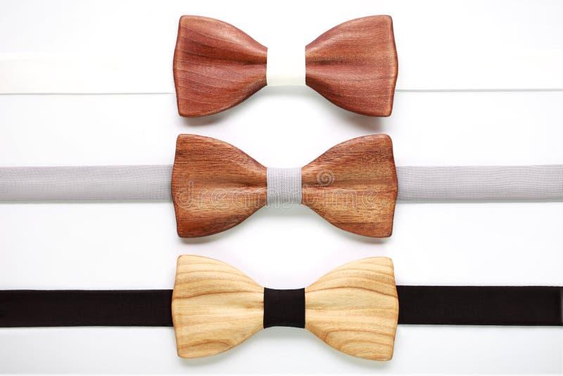 Três laços de madeira com as fitas brancas, cinzentas e pretas Configuração lisa, isolada Team o trabalho, carreira, casamento, c fotos de stock