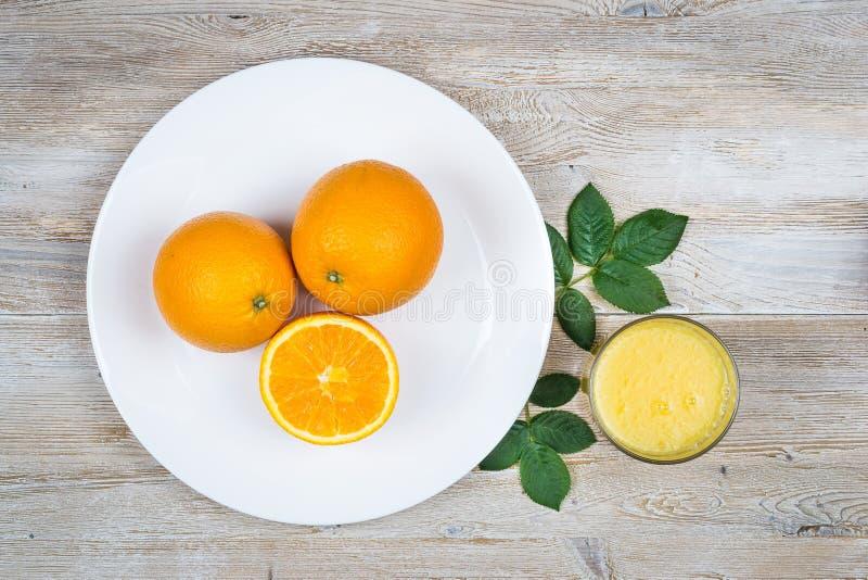 Três laranjas em uma placa ao lado de um vidro do suco em um fundo de madeira claro com opinião superior das folhas imagens de stock royalty free