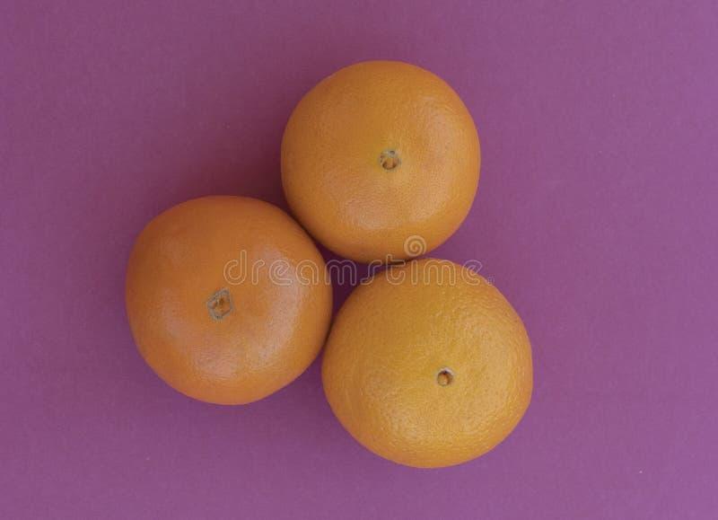 Três laranjas estão para fora próximos um do outro no fundo roxo fotos de stock