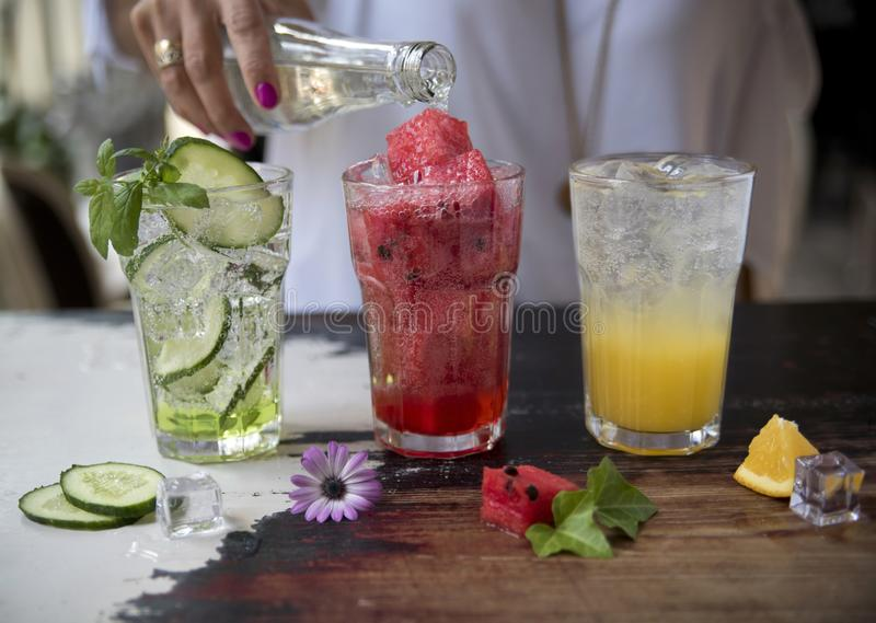 Três limonadas Pepino, melancia e laranja no fundo rústico No fundo a mão de uma menina que derrama a água mineral imagem de stock
