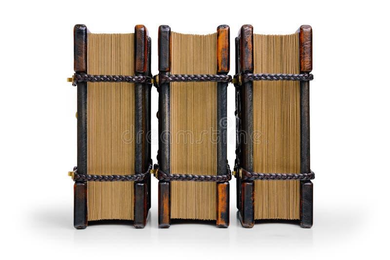 Tr?s livros com placas de cobertura de madeira e os cantos de couro, travados com as correias de couro tran?adas est?o at? a tabe foto de stock