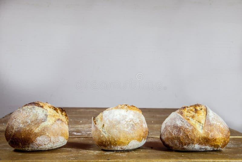 Três loafs pequenos do pão francês na exposição em uma tabela de madeira rústica, estilo do baguette T fotografia de stock royalty free