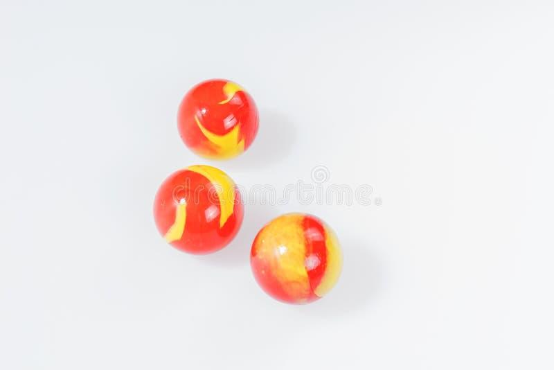 Três mármores amarelos vermelhos no branco fotografia de stock royalty free